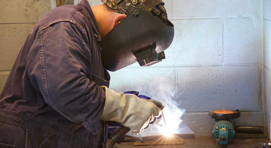 Young craftsman in the process of welding.